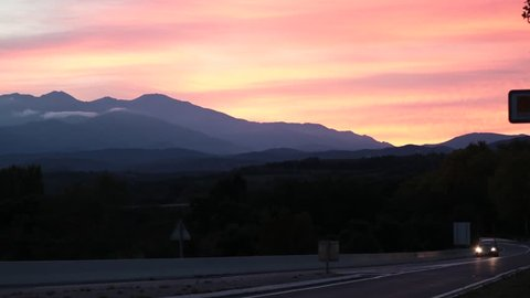 Car traffic on the road at the border between France and Spain at sunset in the Pyrenees orientales, France