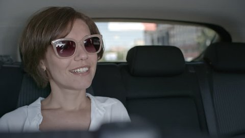 View from the inside of taxi car of beautiful businesswoman sitting on backseat, smiling while telling something to driver and then taking off sunglasses