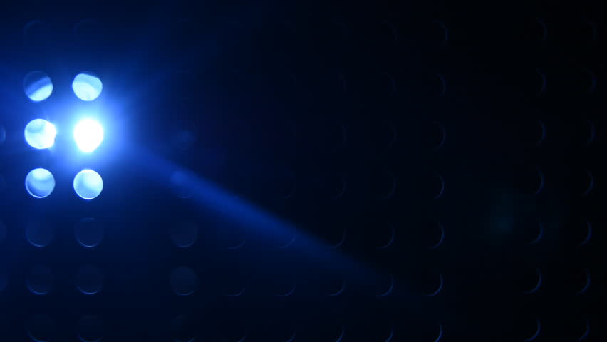 Movement of the light of the blue lantern on a dark perforated background