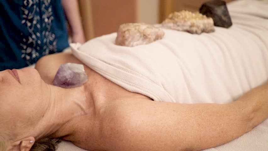 Very tight shot of therapist using a crystal pendulum over a patient's head for mystical