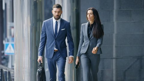 Male and Female Business People Walk and Financial Matters. They're Work in the Central Business District. Shot on RED EPIC-W 8K Helium Cinema Camera.
