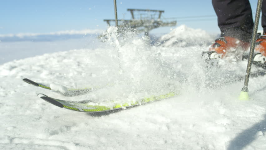 SLOW MOTION CLOSE UP: Skier cleans fresh snow from his skis on a top of the mountain above fog. Ski resort situated in the Alps, Europe on a sunny cloudless winter day. Modern ski lift in background