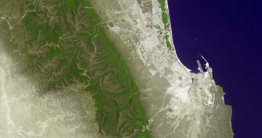 Very high-altitude overflight aerial of Salalah, Oman, and adjacent Qara mountains . Clip loops and is reversible. Elements of this image furnished by NASA