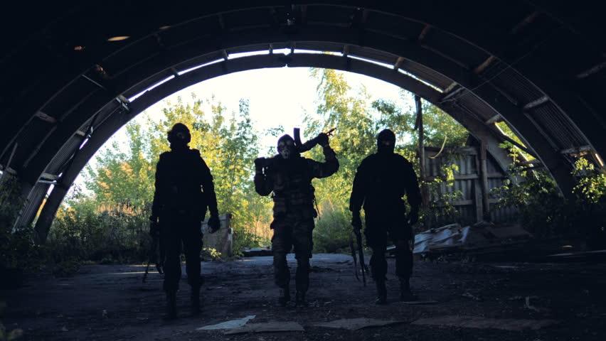 Dark shapes of soldiers walking at ease.
