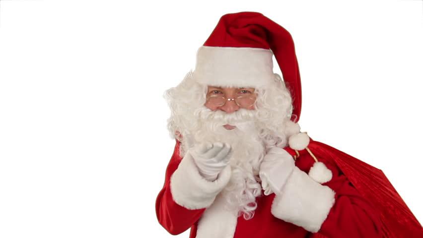 Santa Claus carrying his bag, is looking at the camera, sends a kiss and wave,