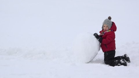 Little child pushing a big snowball, determined boy do his job, colorful life
