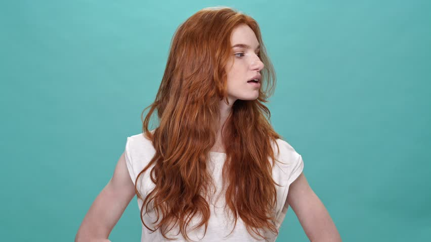 Confused ginger woman in t-shirt shrugs her shoulders and looking at the camera over turquoise background