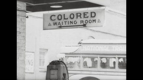 CIRCA 1943 - The colored entrance to a bus station and the White House of the Confederacy are shown as well as traffic and pedestrians walking in a crosswalk in downtown Richmond, Virginia.E