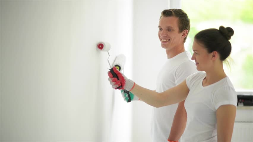 Side View of Happy Smiling Couple Painting the Wall with White Paint in Their Living Room Together. Woman and Man Wearing Bright Shirts and Holding Platens in Hands.   Shutterstock HD Video #31660894