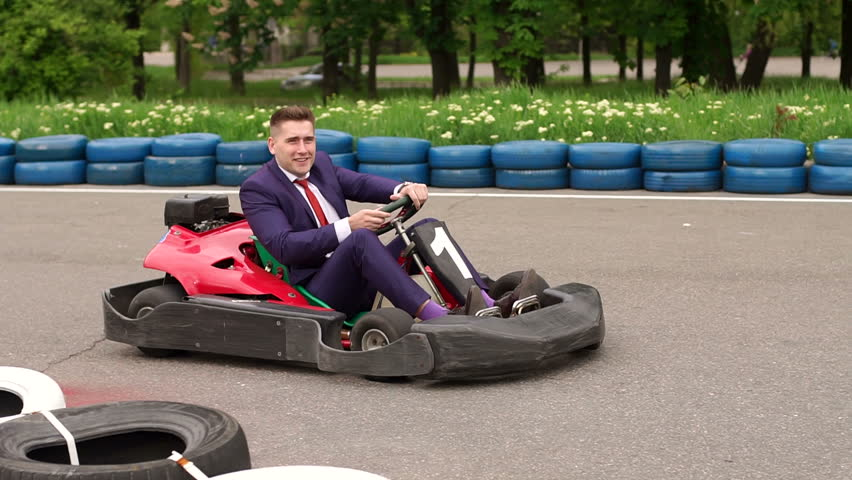 Funny young businessman in a suit driving Go-Kart car in a playground racing track.