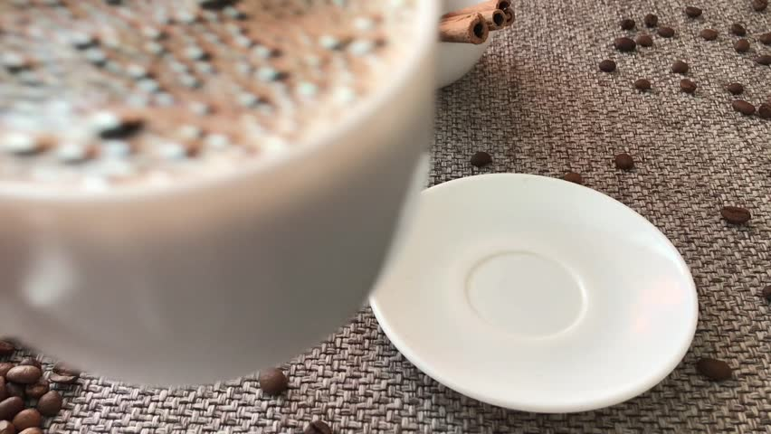 Testi Cup hot drink hand cofee steam cinnamon sticks over black background White cup with black hot coffee standing brown, roasted beans on sacking close hot coffee aroma spreads grain fragrant coffee