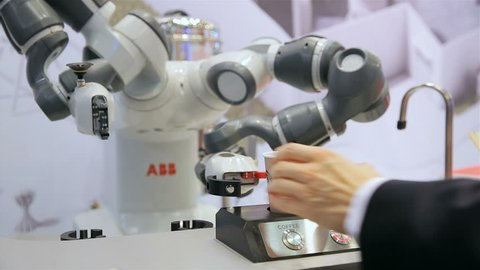 HELSINKI, FINLAND - OCTOBER 10, 2017: Robot with flexible hands makes a coffee. Latest technology in the field IoT, VR, AR, Big Data on the Trade Fair TEKNOLOGIA 17 in Messukeskus expo center.