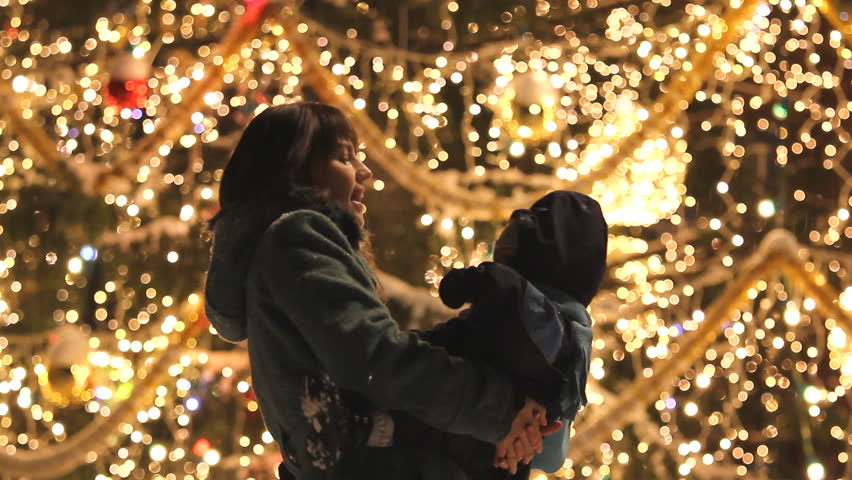 Mother and baby dancing and having fun during Christmas night in front of the decorated big tree full of colorful sparkling lights