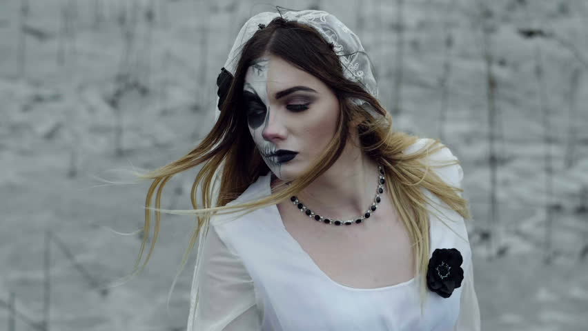 The young woman with frightening make-up of dead bride for Halloween dressed in a white wedding gown going through the field of dried grass. Slow motion. HD | Shutterstock HD Video #31696990