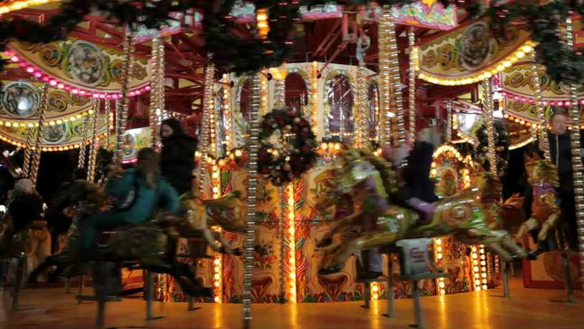 EDINBURGH, SCOTLAND - DECEMBER 16: Revelers riding a carousel at the Christmas Fair in Princes Street Gardens on Dec 16, 2012, an attraction enjoyed by thousands of visitors to Edinburgh each year.