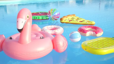 CLOSE UP: Empty inflatable flamingo, pineapple, pizza, doughnuts and watermelon floaties floating on pool water. Fun colorful floats waiting for pool party on hot summer vacation day.
