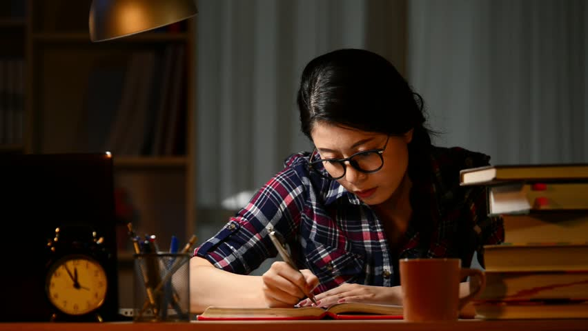 Young student at home desk reading and yawning tired at night with pile of books and coffee cup preparing exhausted an exam in university education concept. | Shutterstock HD Video #31707370