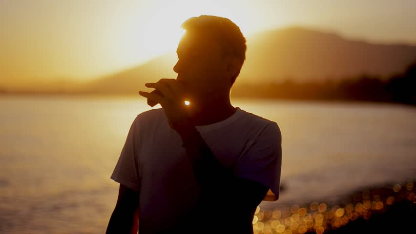 A guy at sunset smokes a e-cigarette. Vape. Vapping. Sea / Ocean / mounting / beach The guy pours liquid into the electronic cigarette and smokes