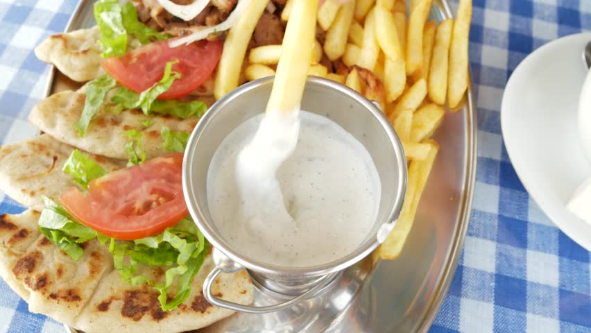 Souvlaki Greek meat kebabs in pita bread with sauce, vegetables and French fries. close-up of a hand dipping a slice of french fries into a white sauce. 4k