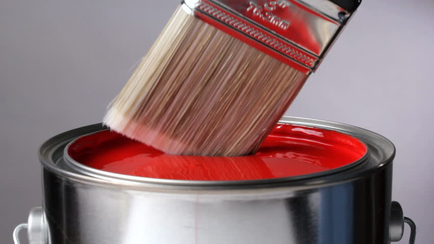 Paint brush dips into can of red paint