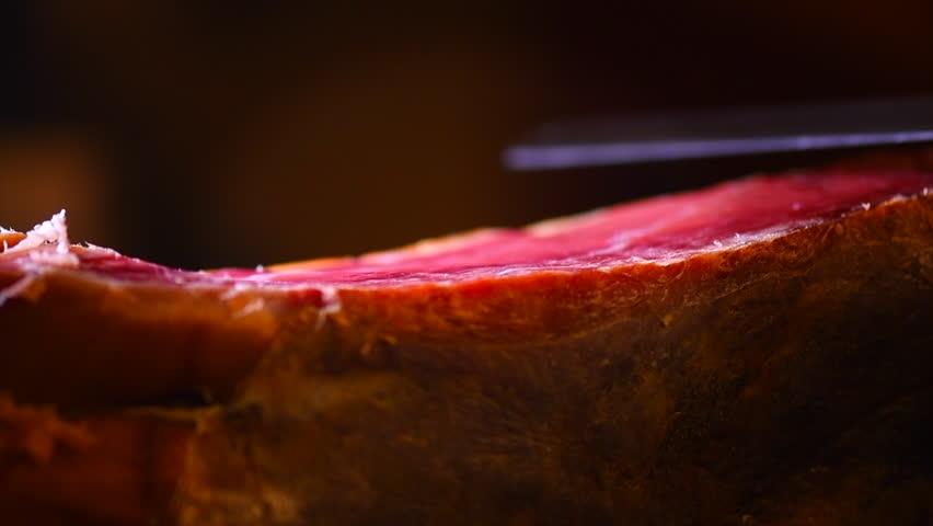 Jamon. Jamon serrano. Traditional Spanish ham on black close up. Slicing Hamon iberico. Prosciutto close up. 4K UHD video 3840x2160
