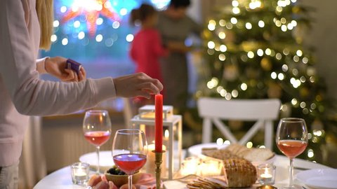Family Christmas Meal. A young woman lights the candles at the Christmas table. Grandma and granddaughter decorate the Christmas tree
