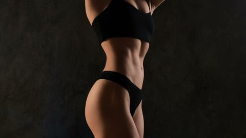Muscular young woman in studio on dark background shows the different movements and perfect body parts. Abs and buttocks close-up