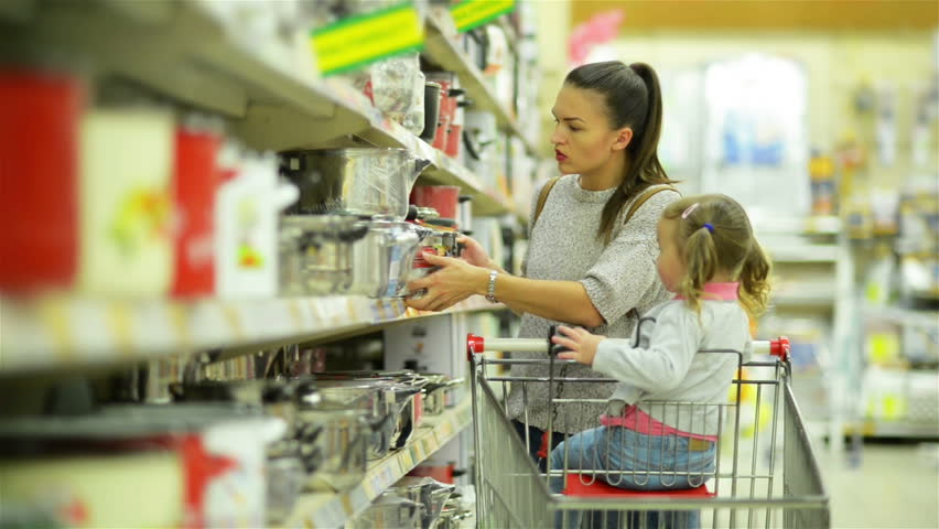 Happy Female Child and Her Attractive Mother Inside the Hypermarket Choosing Some Dishes or Pans Together Standing near Supermarket Shelf.