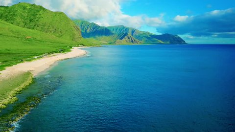 Colorful Aerial: Lush Hidden Hawaiian Tropical Island Beach with White Sandy Beach, Green Mountains, Gorgeous Blue Ocean Water, Blue skies, on Oahu Hawaii, rugged reef, swimmers, Vibrant sexy beach.