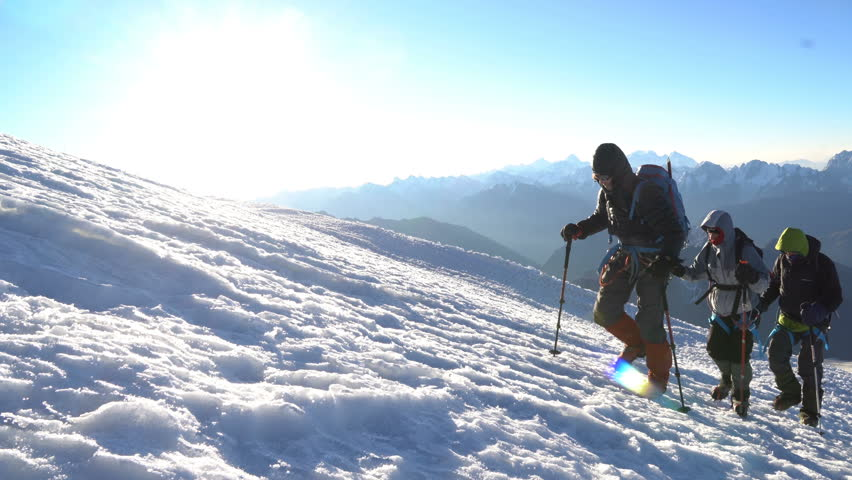 Three Climbers in crampons coming up to the summit of Elbrus. Snow peak.