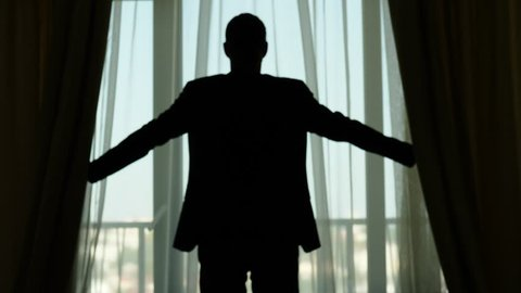 Guy stay against fabric draperies, quickly stretch out hands holding edges and open curtains. Silhouetted half length view from back, slow motion shot. Man wear casual suit