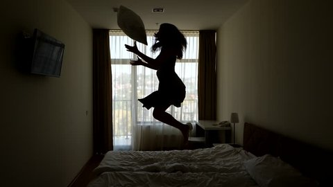 Amused woman happy jump on bed, toss up pillow, black silhouette against room window. Slow motion shot, pure happiness from carefree lady, bounce at bedroom