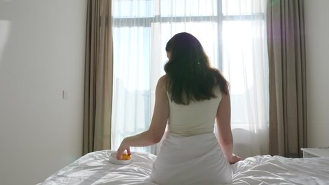 Young adult woman relax at sunny weekend morning, sit up on cozy soft bed, take apple from cup and bite it. Slide camera motion left and back, bright white bedroom. Sun flash through zephyr curtain