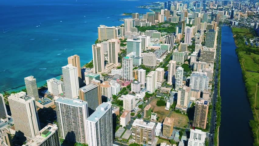 Colorful Aerial View of Ala Wai Canal with Buildings, Condos, Hotels, and business in Waikiki, Honolulu Oahu Hawaii Island.  Blue Ala Wai Canal River beside green golf course vegetation. Outrigger.