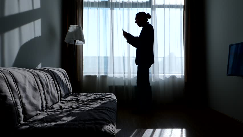 Bored and boiling man hold two phones and swear to, black silhouette against room window. Guy finish bad conversation and shout after to express angry emotions. Simple minimalist modern apartments | Shutterstock HD Video #31814590