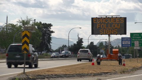 LED Road Sign: Evacuees Follow Signs - Extreme Fire Hazard - Please Use Caution. Along highway during extreme fire season in British Columbia. Vernon, BC. Med Shot