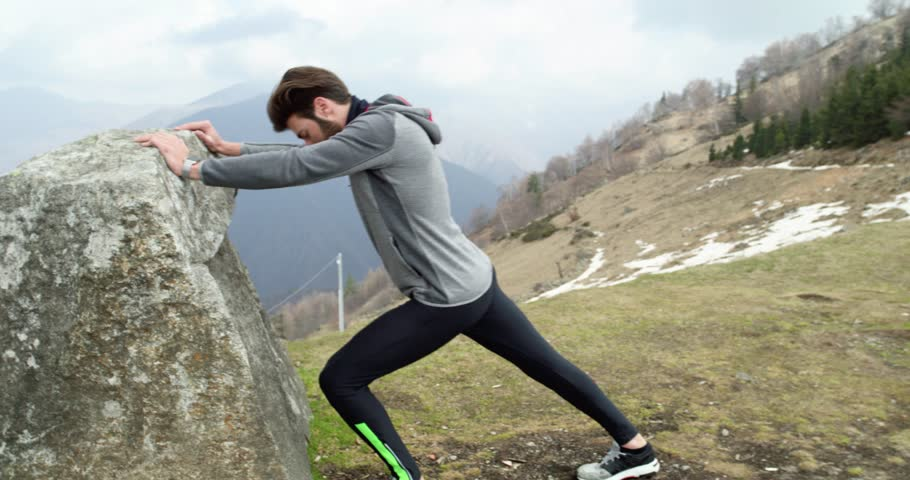 Athlete man runner warming up or cooling down stretching.Real people adult trail running sport training in autumn or winter in wild mountain outdoors nature, bad foggy weather.4k video   Shutterstock HD Video #31837930