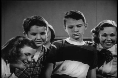 CIRCA 1951 _ A group of students evaluate a healthy and unhealthy classroom guinea pig.