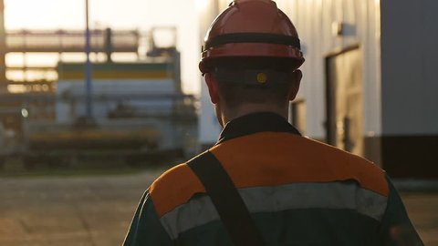 slow motion backside view skilled worker in outfit walks along huge refinery territory under sunshine