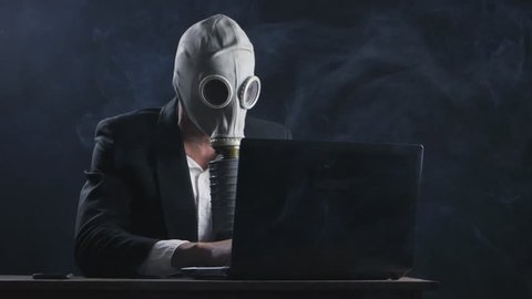 businessman in gas mask working at laptop in office in smoke