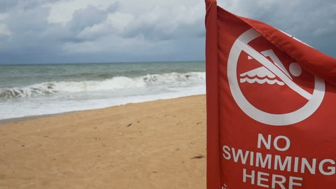 4K. no swimming sign for security information on the beach. the red flag for warning  that the water in this area is prohibited. the environment is not safe for swimming.