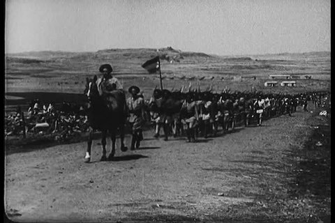 CIRCA 1940s - The Abyssinian Army marches, fires artillery and salutes Emperor Haile Selassie, during the British African Campaign, in World War 2, in 1943.