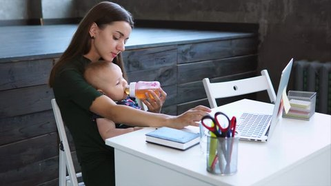 Woman with dark hair is watering her little child from a bottle. She is sitting in a modern room at a table, laptop, diary and stickers are lying on a table.
