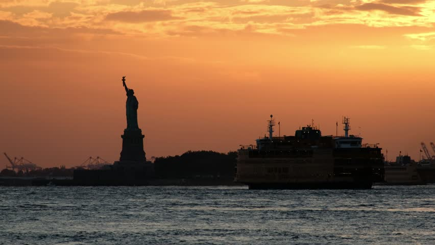 Sunset at the Staten Ferry boat crossing the Hudson River with the silhouette of the Statue of Liberty in the background