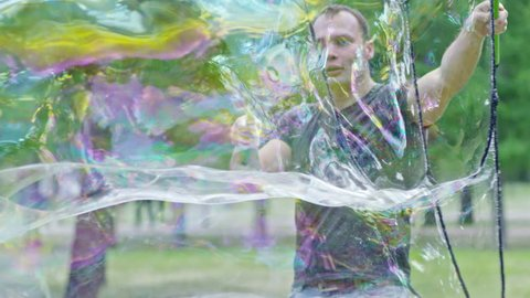 SLOWMO of professional performer blowing long rainbow-colored soap bubbles with tri-strings wand in the park