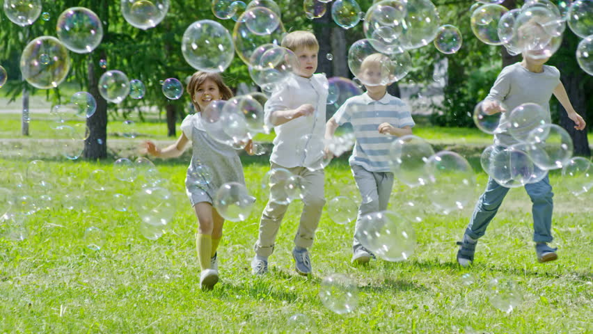 Tilt up slowmo of joyous little boys and girl running towards the camera through lots of soap bubbles flying in the air while playing on green lawn in the park | Shutterstock HD Video #31898920