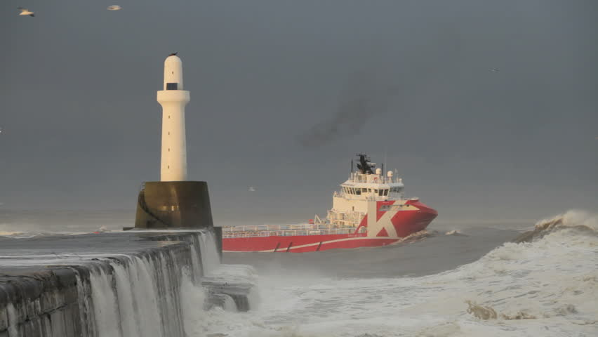 ABERDEEN, SCOTLAND - DECEMBER 23: Boat leaving Aberdeen harbour in heavy seas on December 23, 2012. One of the busiest ports in Europe, the harbour provides support for the North Sea Oil industry.