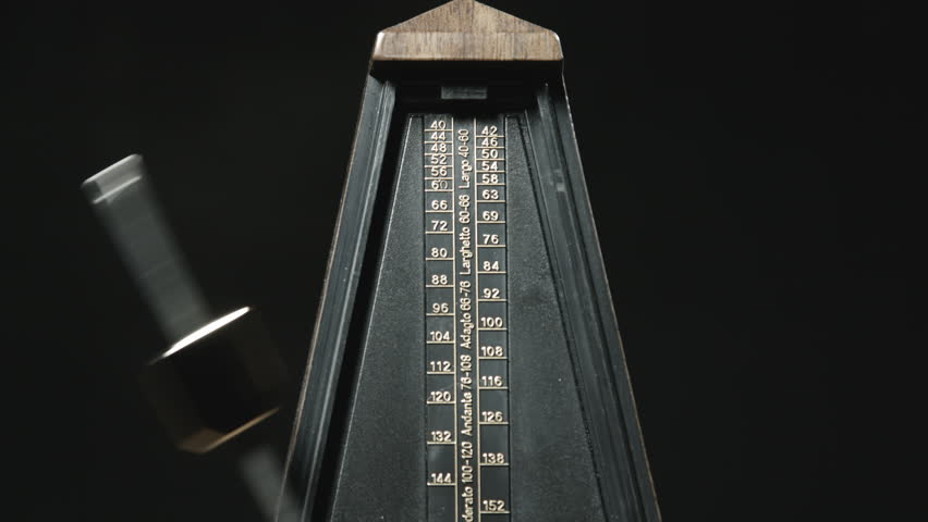 Old steam engine locomotive train with freight rail cars moving on close up shot of vintage metronome with golden pendulum beats slow rhythm on the dark malvernweather Images