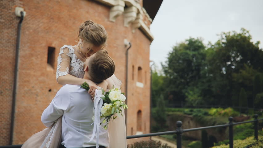 Wedding pair  looking each other into the eyes and kissing  in the park. Ethno wedding dress and embroidered shirt.