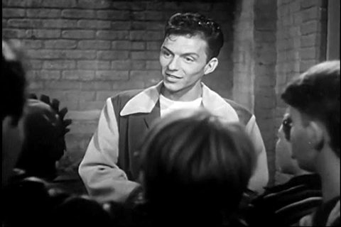 CIRCA 1940s - Singer Frank Sinatra sings (What Is America To Me?) The House I Live In to a gang of reformed juvenile delinquents in an alley, in 1945.